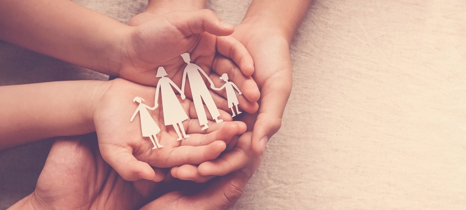 Adult and children hands holding paper family cutout, family home, foster care, homeless support concept